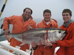 Fishermen (and one BIG fish) in orange foul weather gear