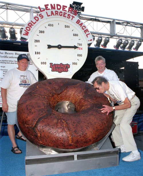 FILE - In this July 24, 1998 photo, Murray Lender kisses the world's largest bagel while baker Larry Wilkerson, left, and Lender's Bagel Bakery manager Jim Cudahy watch after the weight of the bagel was revealed during Bagelfest in Mattoon, Ill.  Murray Lender, who helped turn his father's small Connecticut bakery into a national company that introduced bagels to many Americans for the first time, has died in Florida. He was 81. Lender's wife, Gillie Lender, tells The Associated Press that her husband died Wednesday, March 21, 2012 at a hospital in Miami from complications from a fall he suffered 10 weeks ago. The couple lived in both Aventura, Fla., and Woodbridge, Conn.  (AP Photo/Journal Gazette, Doug Lawhead)